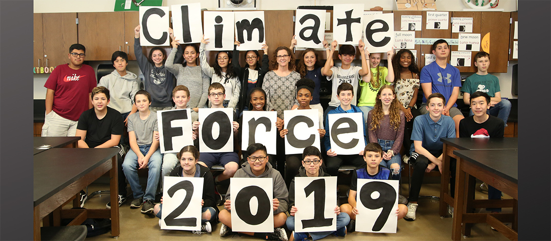 Terri Skinner and her class display Climate Force 2019 sign.